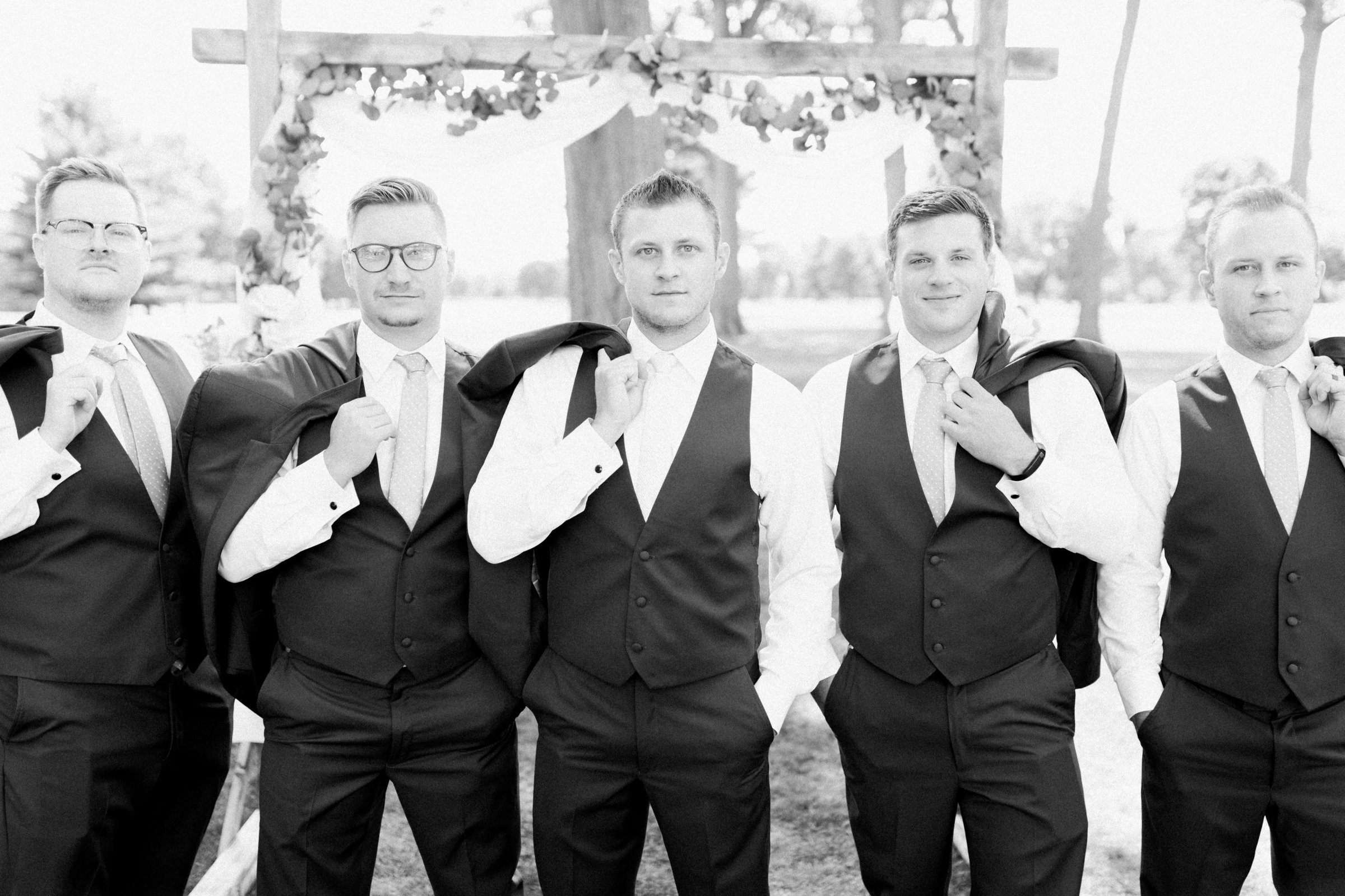 groomsmen pose for a portrait in front of the ceremony arch at Owosso Country Club in Lansing photo by Wedding Photographer in Grand Rapids, Cynthia Boyle