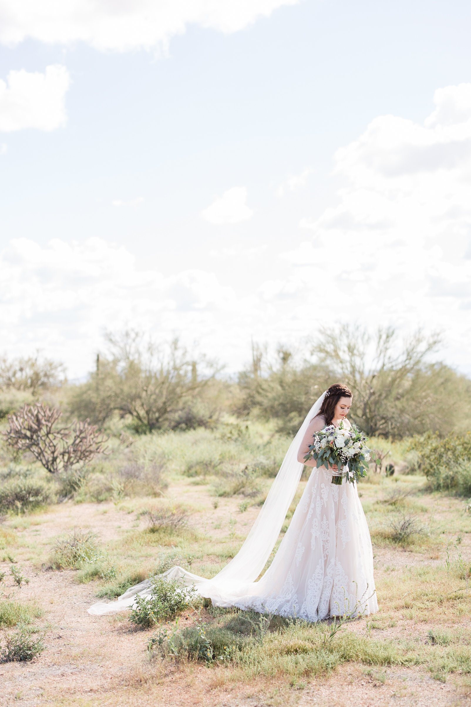 Bride takes time to think while standing in the desert