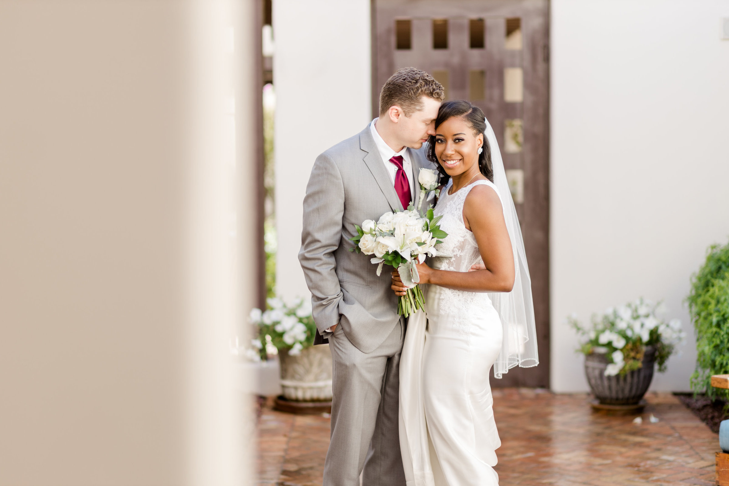 A Bride and Groom kiss during their first look at the Wigwam Resort and Spa