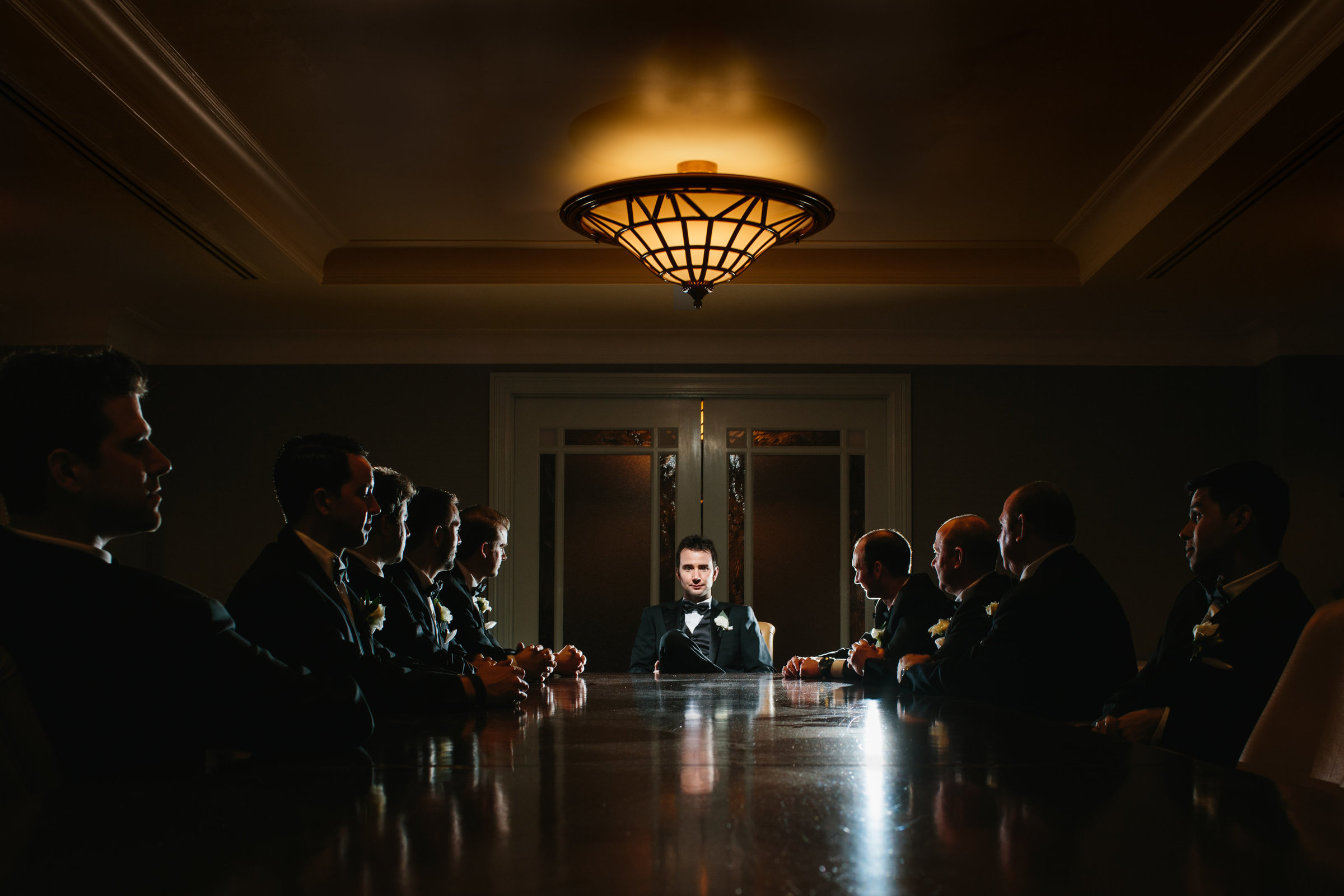 A groom and his groomsmen sitting at a conference table in dramatic creative photo