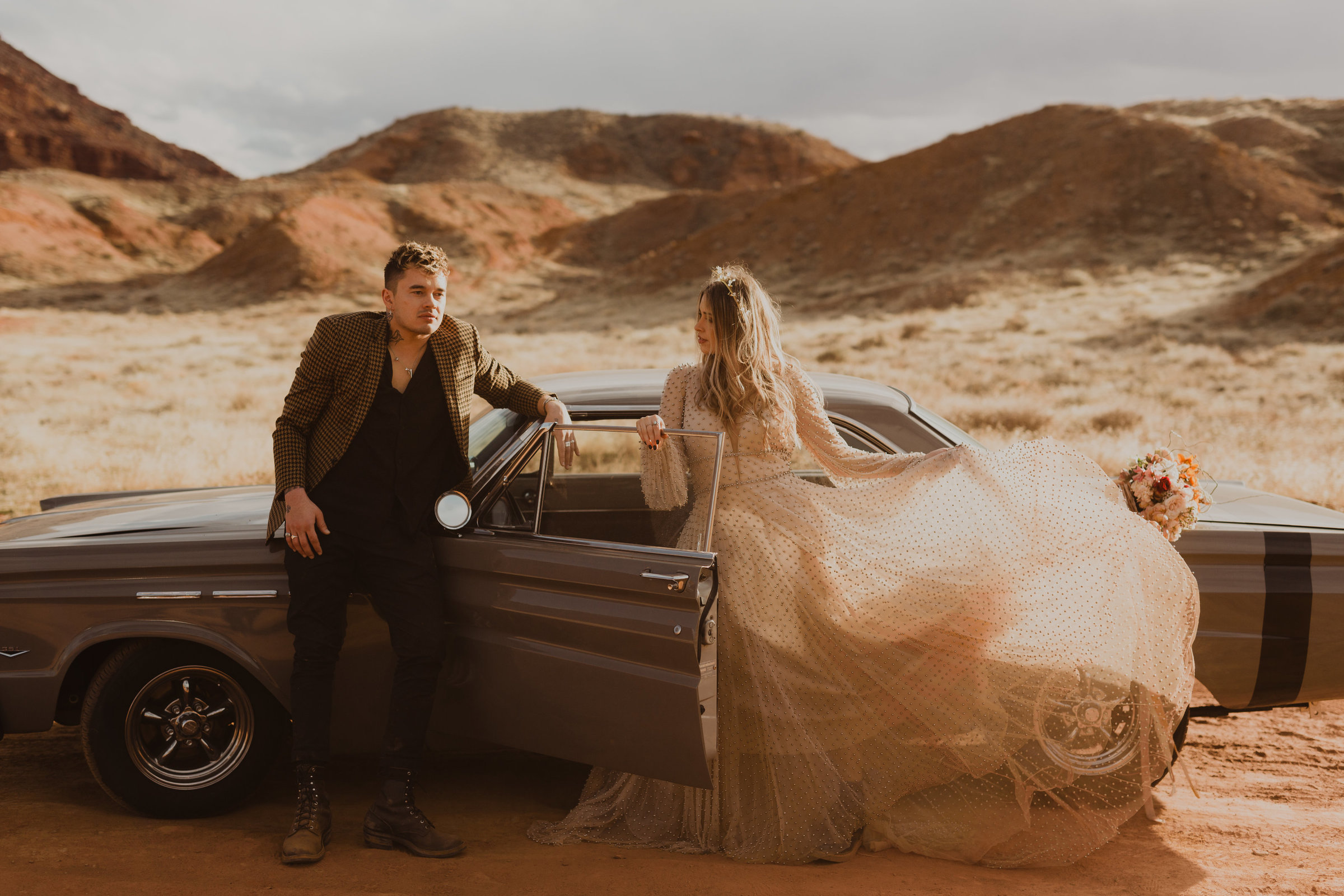 bride and groom posing in front of their vintage car in castle valley moab utah