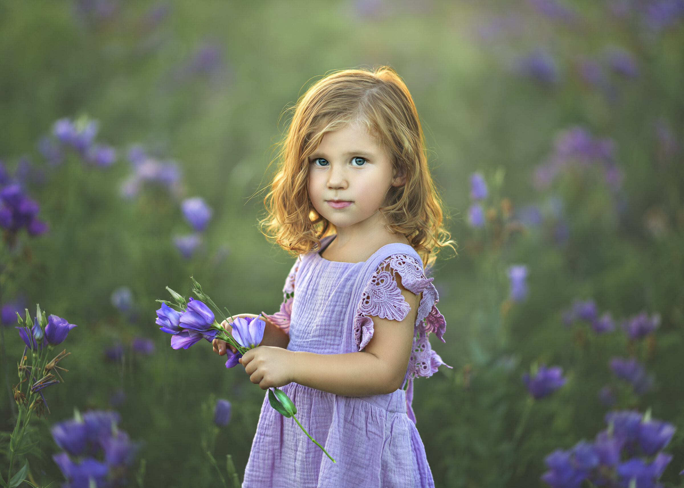 Fine art portrait photograph of little red head girl with curls in a  purple linen dress wit texas bluebell flowers in Crandall, Texas