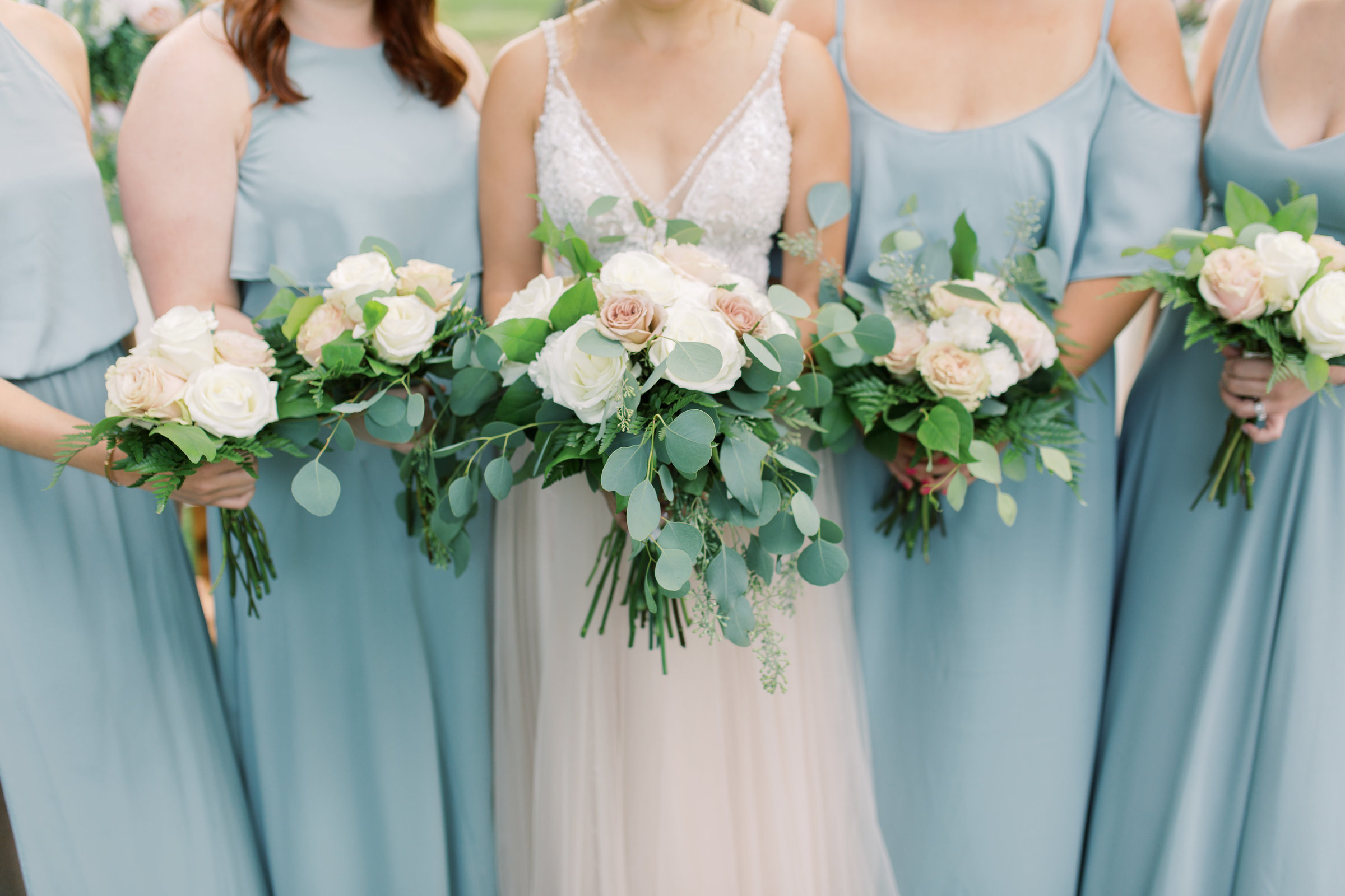 Bridesmaids in blue dresses hold their white and pink bouquets, photo by Wedding Photographer in Grand Rapids, Cynthia Boyle