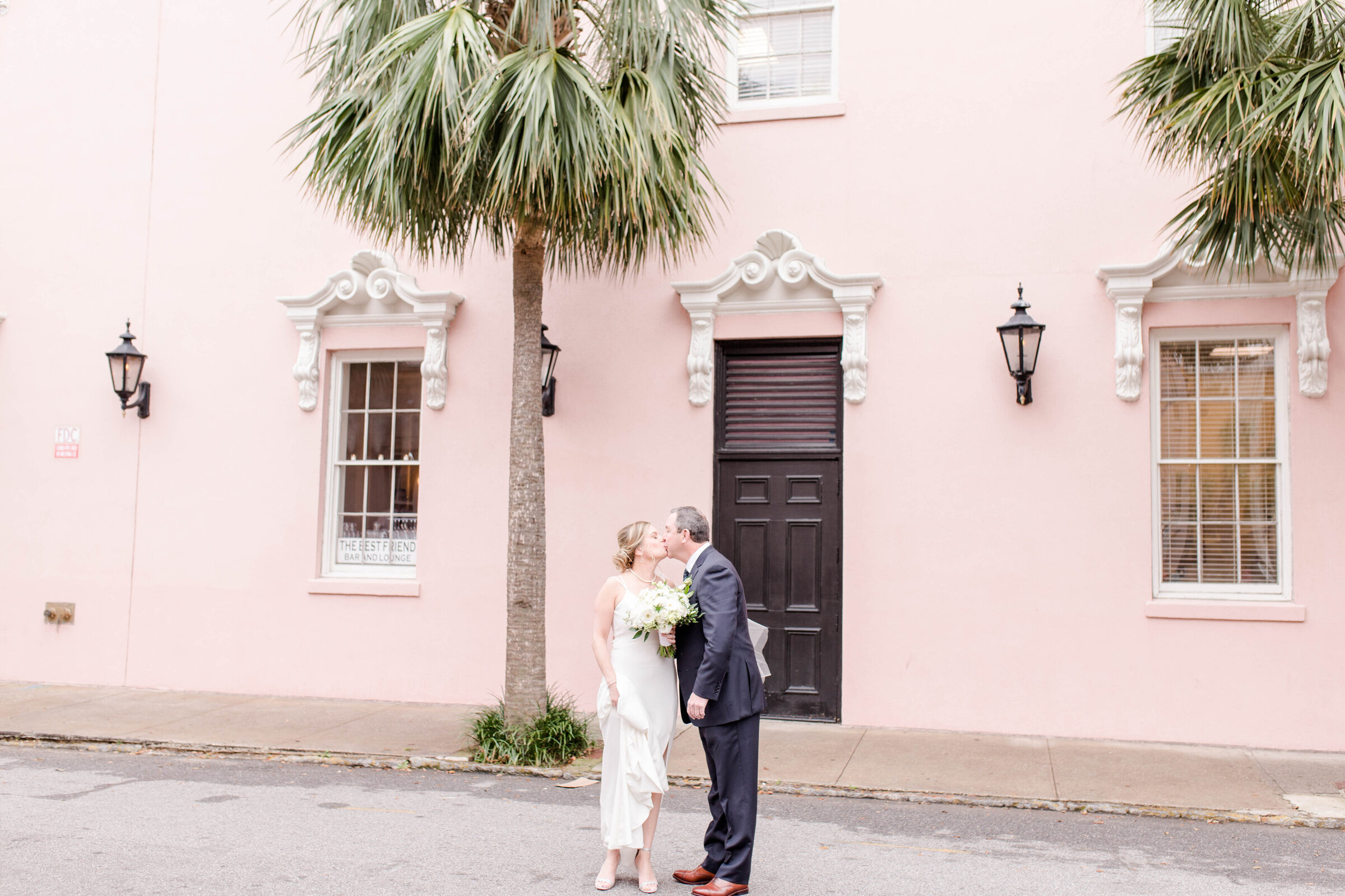 bride & groom kissing at the mills house pink wall