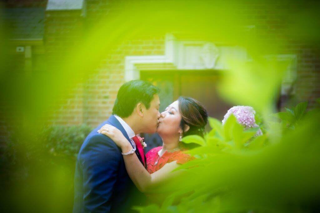 Bride and groom kiss on their wedding day before a Chinese Tea Ceremony. The bride is wearing a red dress, as is tradition. The photo's edges has a green leaf and the couple kissing appears in the middle. Photo taken by Sacramento wedding photographer Philippe Studio Pro.