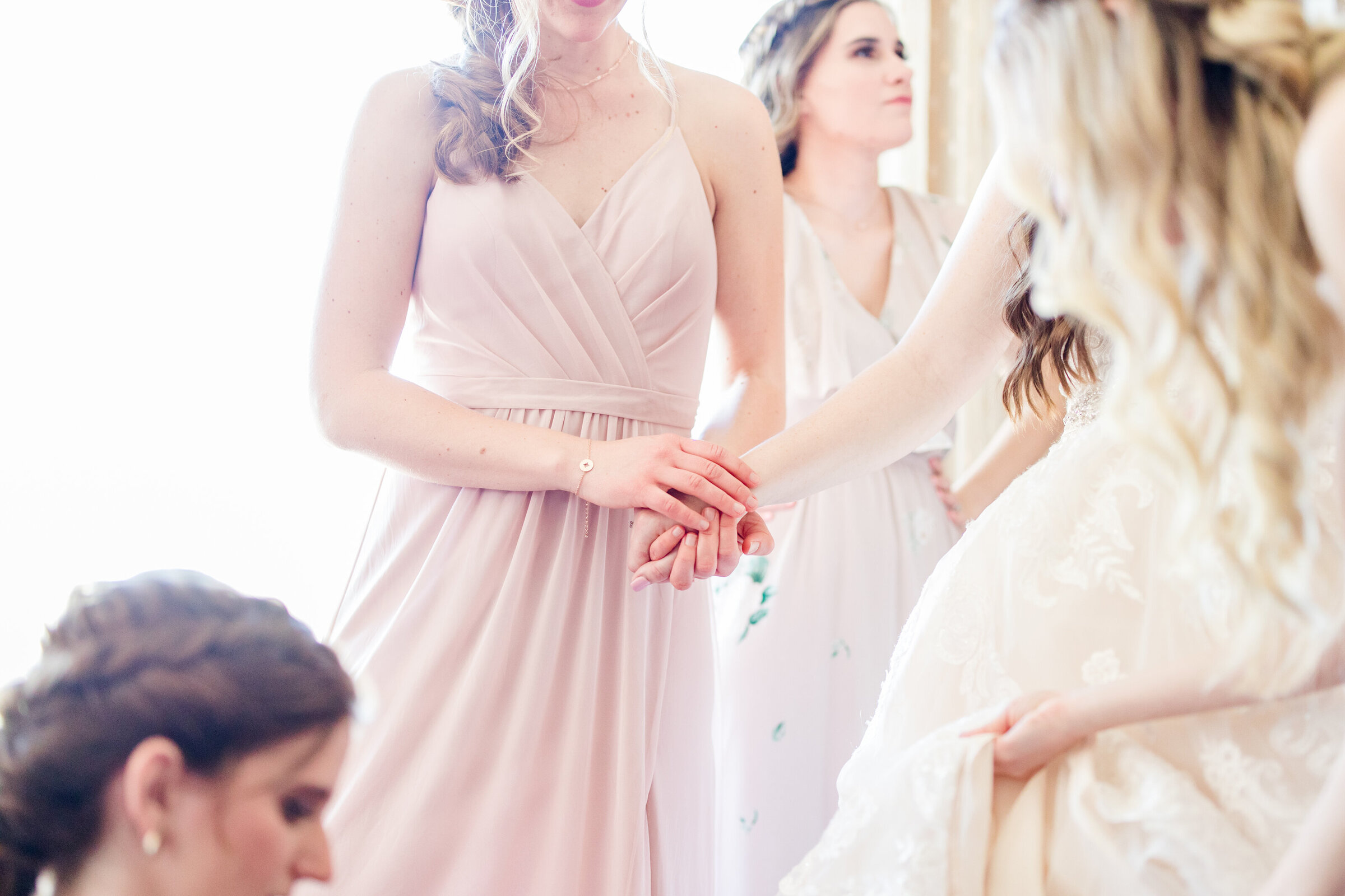 A bride holds the hand of a bridesmaid during an emotional moment
