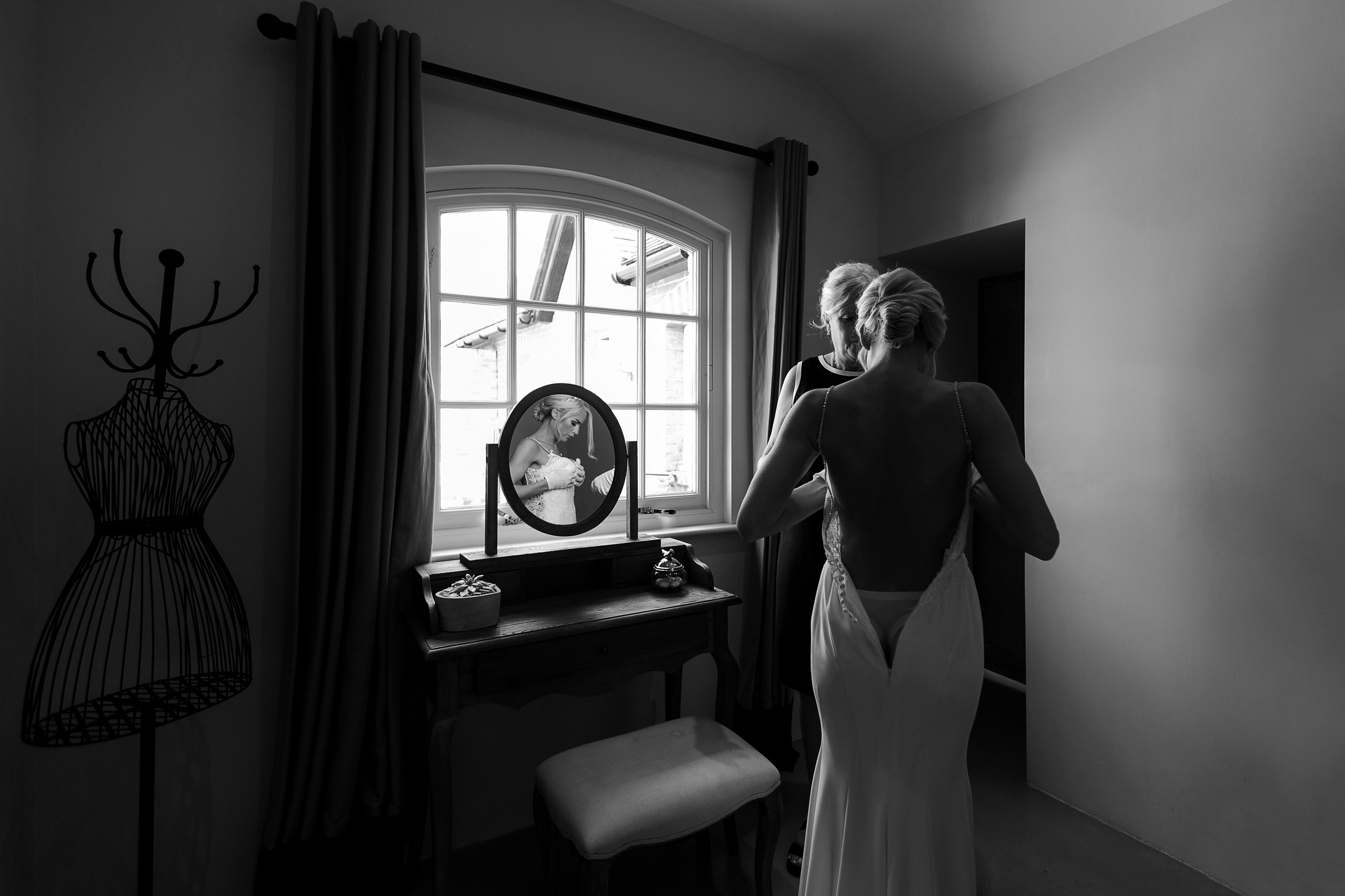 Stunning natural light black and white wedding photography by Adorlee of this beautiful bride getting ready for her wedding and doing up her Enzoani gown and reflection in the dressing table mirror
