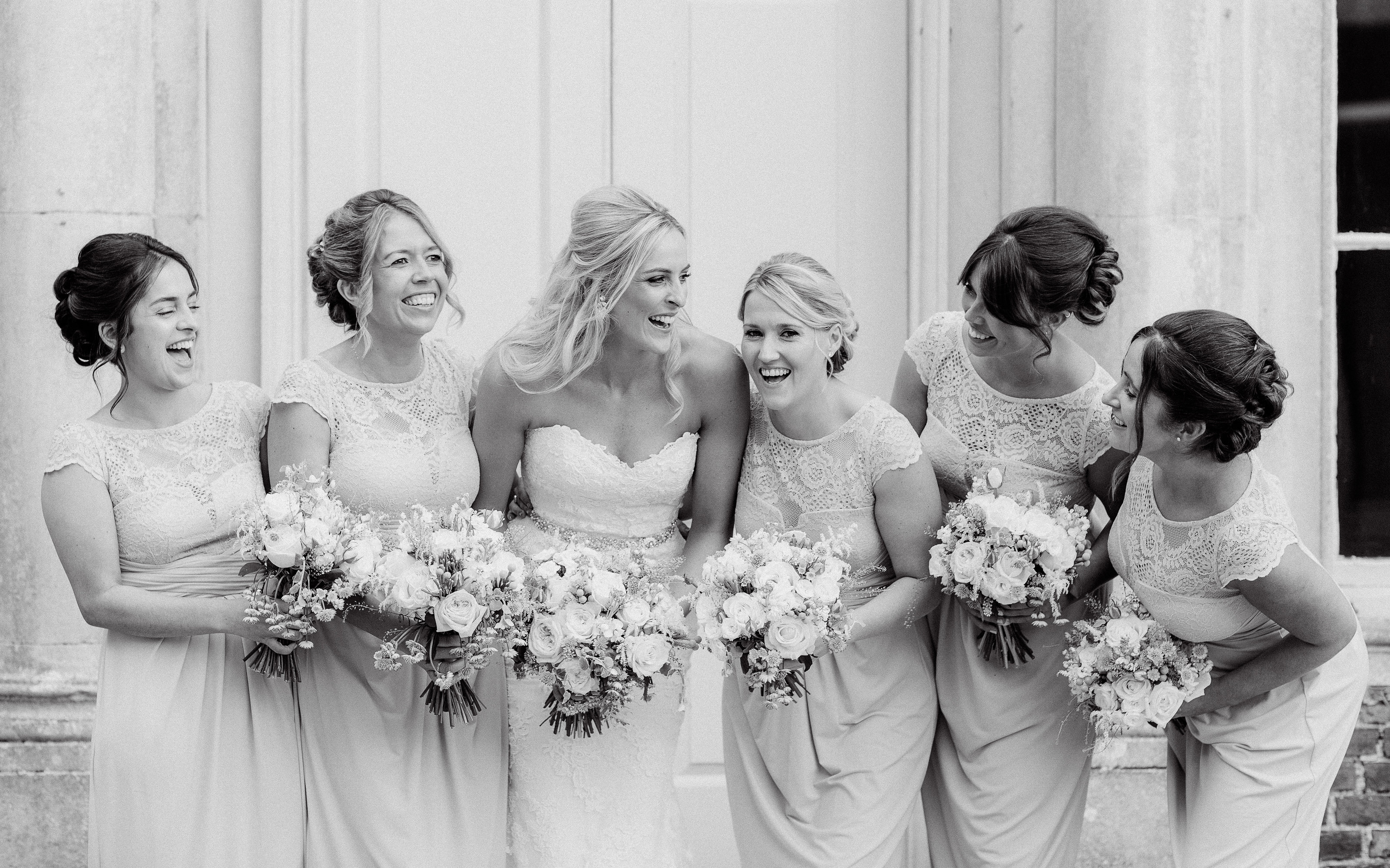 Beautiful bridal party looking at each other laughing in this black and white photo taken by Adorlee Photography in Chichester of Bridesmaids gone wild