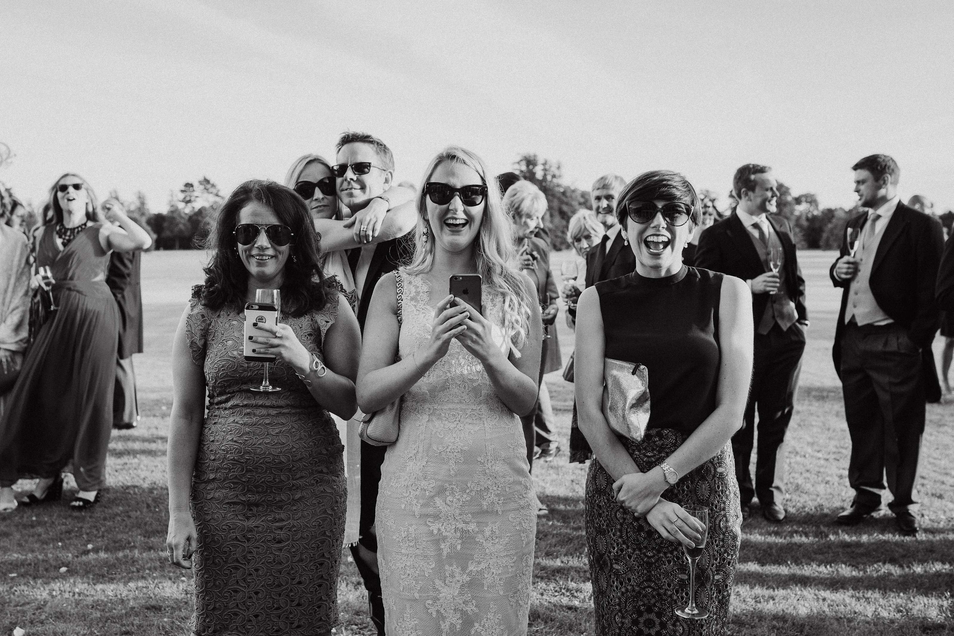 Three guests laugh in this candid black and white moment captured by Adorlee Photography at Goodwood House in Chichester