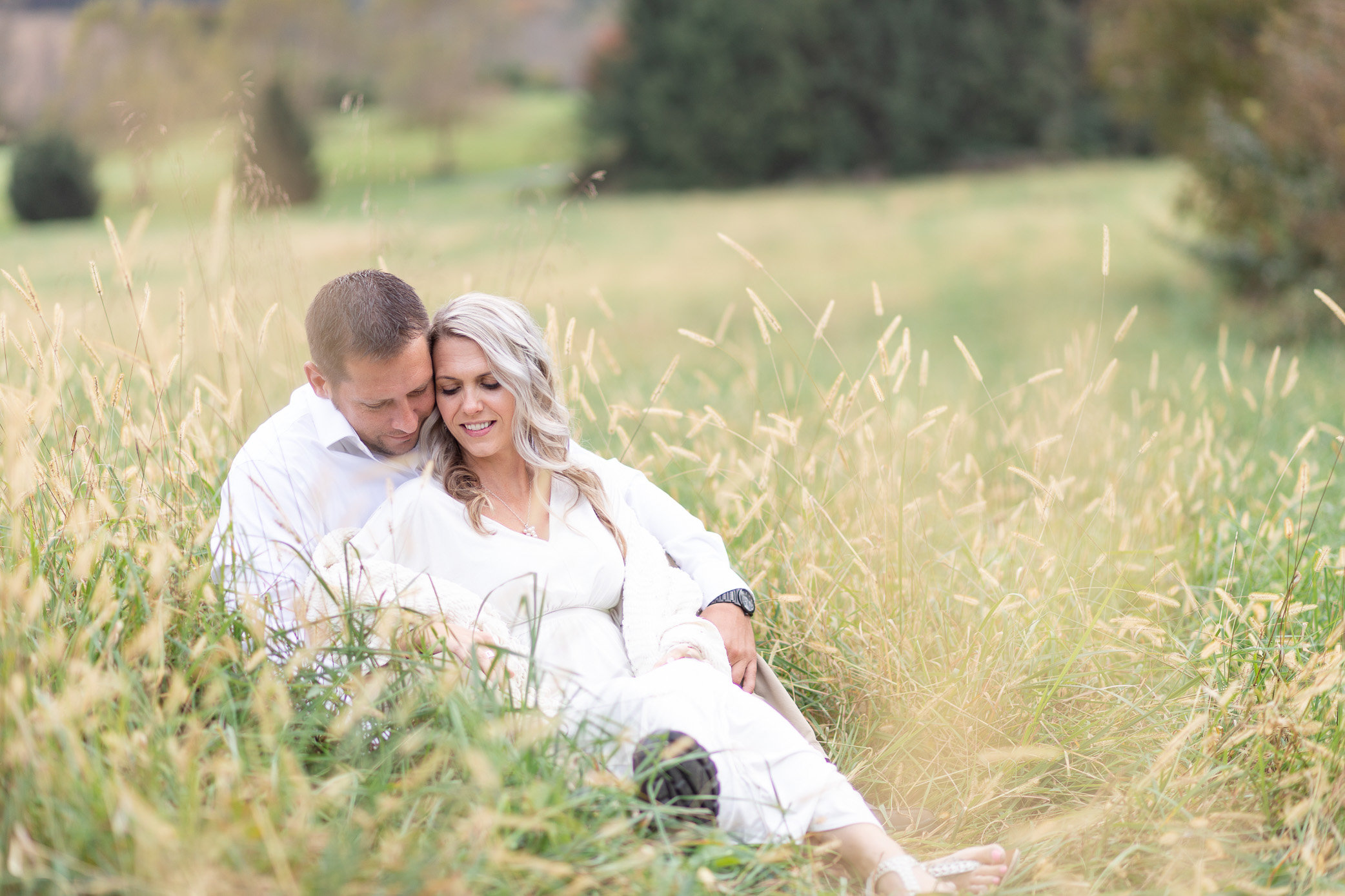 Rebecca and Scott sitting in a field of golden grass