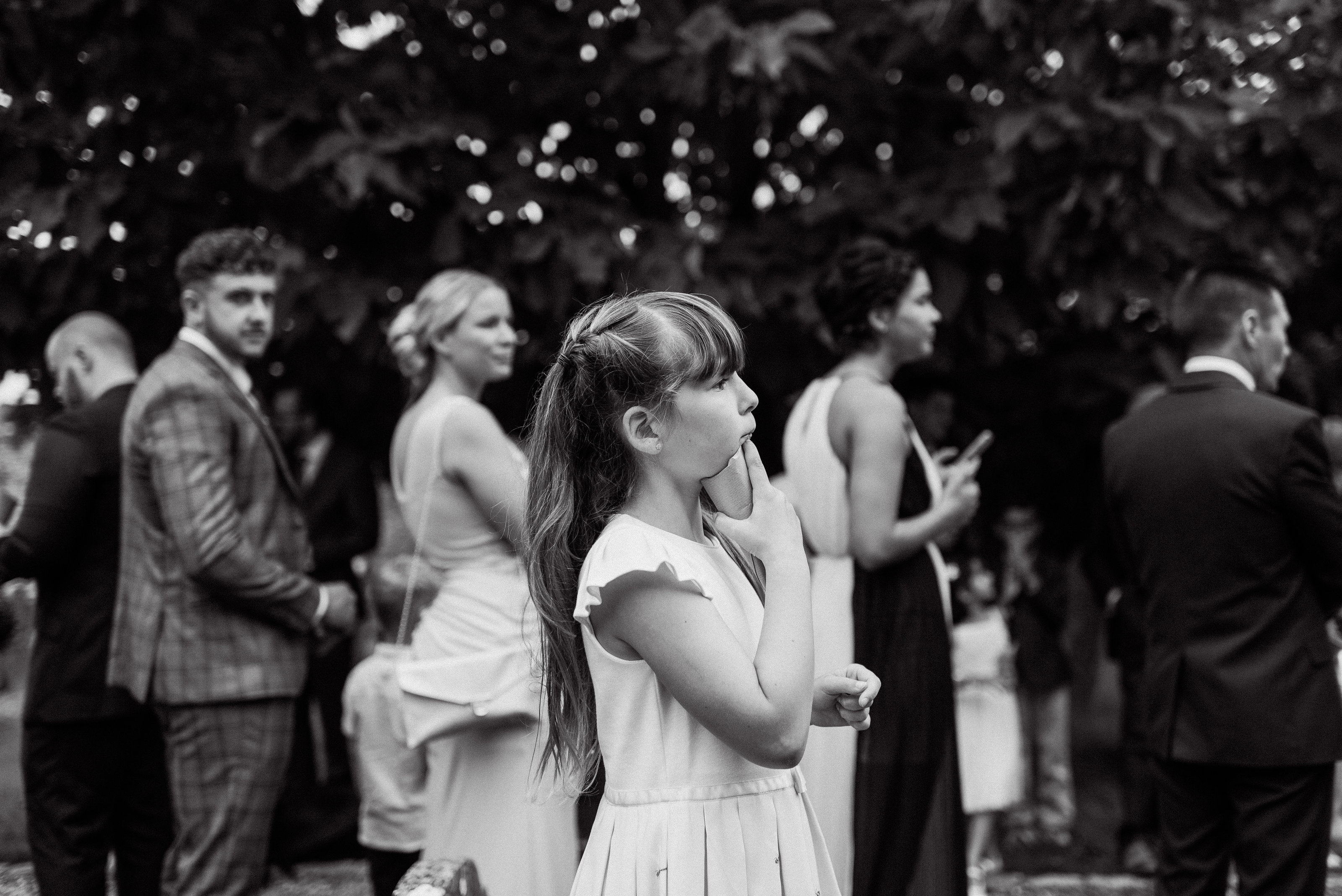 Candid black and white photograph of flowergirl holding confetti eagerly waiting to throw the confetti, captured by Adorlee Photography