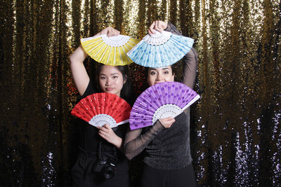 two women playing with colorful fans.