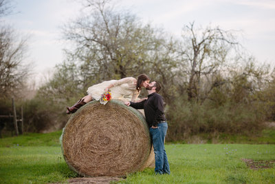 groom kissing his bride while she is on a hay bale at Hoffman Ranch wedding venue by Expose The Heart Photography