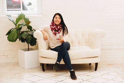 Headshot of Diana Wei Fang of The Finer Points. Diana is wearing a white sweater, dark jeans, black ankle boots, and a red and white patterned scarf. She is sitting on an ivory tufted couch in front of a white brick wall. She is holding a ceramic mug.