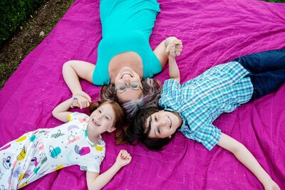 a mom and 2 kids lay on a pink blanket holding hands