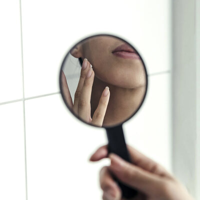 Woman holding mirror skincare brand