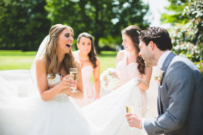 reportage wedding photo of bride and groom laughing with friends at tatton park