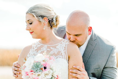 Groom Kissing Bride's Shoulder at Iowa Boho Wedding