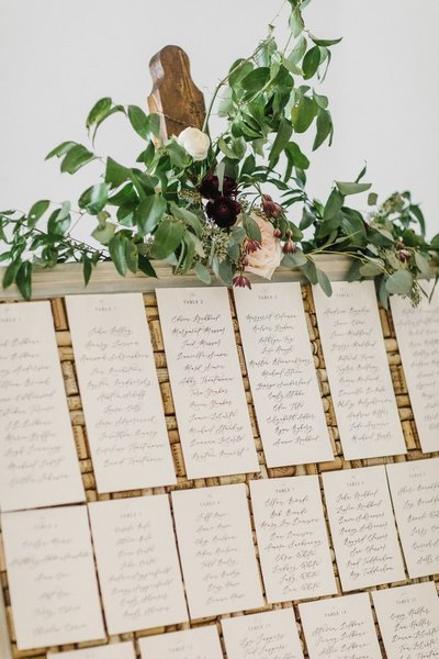 Custom seating chart with calligraphy on a corkboard