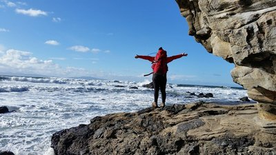 picture of hiker with red backpack standing on light grey rock and looking out at ocean. hiker facing away from camera and in foreground.