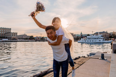 Weddingcouple preshoot in Stockholm city in golden hour. Her on his back smiling to the camera with the flowers high avove their heads.