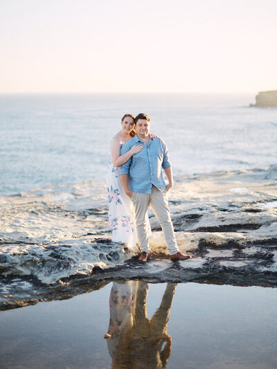 Couple standing on sea cliff in the Royal National Park with ocean behind then during their engagement session by Blue Mountains Wedding Photographer Joshua Witheford