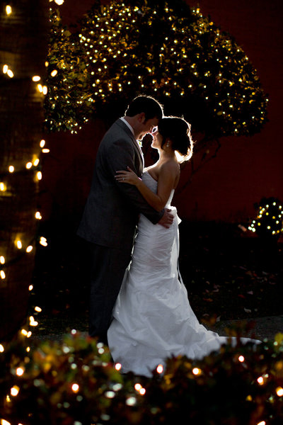newlyweds embrace surrounded by Christmas lights