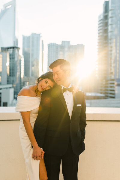 Bride and groom holding hands on the rooftop of the Grand Bohemian Hotel with the sunset photographed by Charlotte Wedding Photographer.
