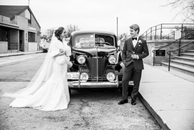 Stylish bride and groom pose with their vintage car in front of a church.