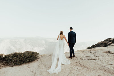 Bride and groom holding hands and standing on a mountain edge