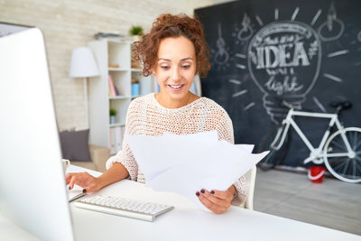 happy-young-woman-reading-business-documents-at-WRQC57Z