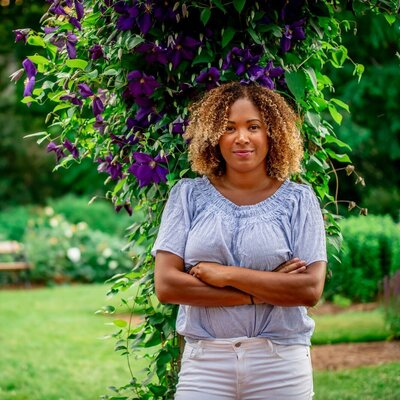woman in blue blouse and white pants facing camera leaning against  purple plant