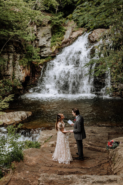 bride and groom standing in front of waterfall