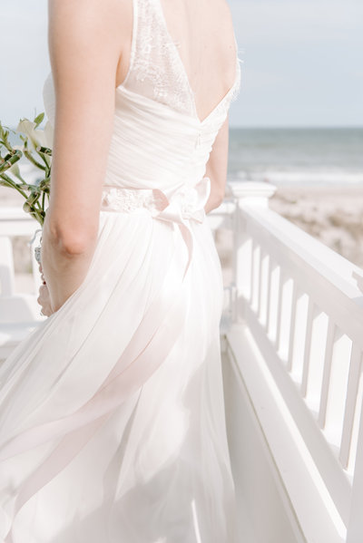 bride's dress is caught fluttering in the beach breeze