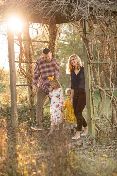 Family of four walking under a trellis with the sunset