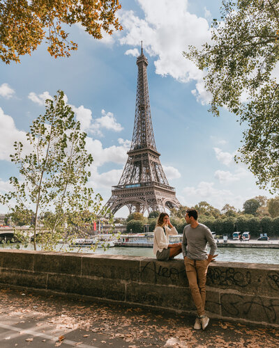man and woman sitting on stone wall with eiffel tower in background