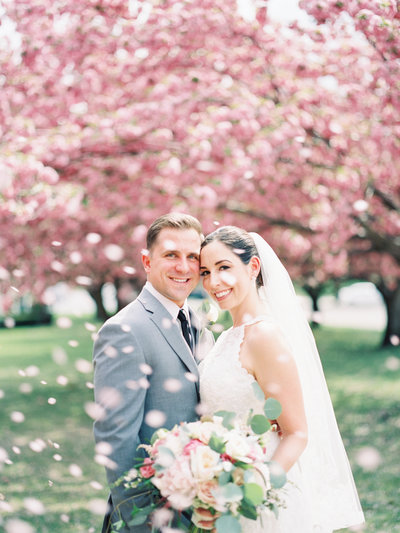 Bride and group embrace in front of cherry blossom trees