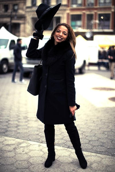 pretty woman in black coat standing in street with hat