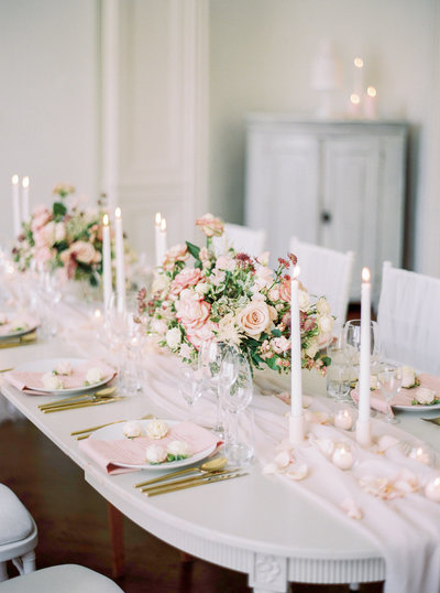 Wedding table setting with light pink flower arrangements, taper candles and flowing fabric. Designed by Swedish wedding planner, designer and florist Linnéa Bergqvist
