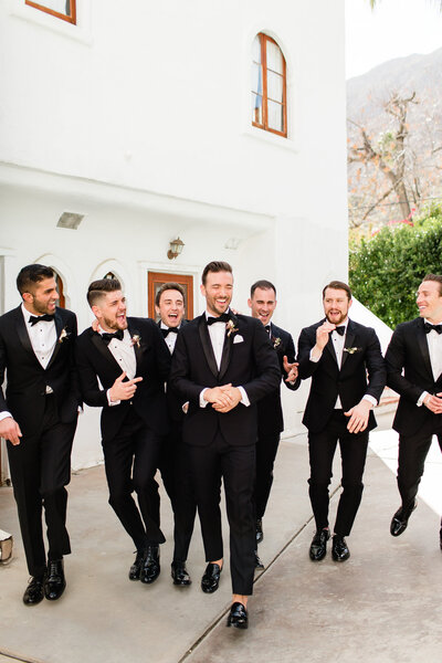 Groom with his groomsmen, walking around Korakia Pensione in Palm Springs, California. Engaged couple kissing in San Francisco, California. Photo taken by Cheers Babe Photo.