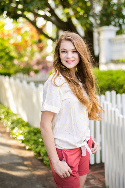 Teen girl in white blouse and pink shorts smiles in front of white picket fence