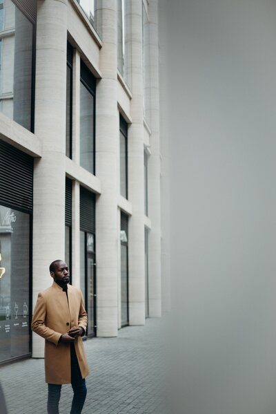 photo-of-man-in-brown-coat-posing-outside-building-3205993