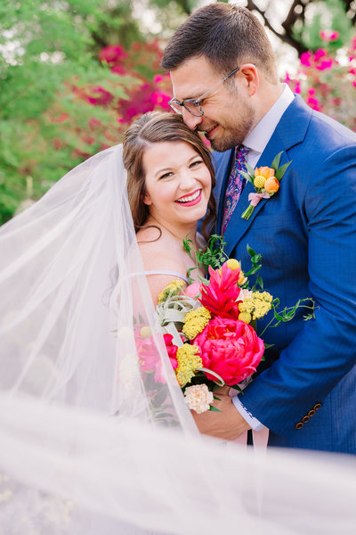 smiling bride and groom wearing blue suit and holding boho bouquet