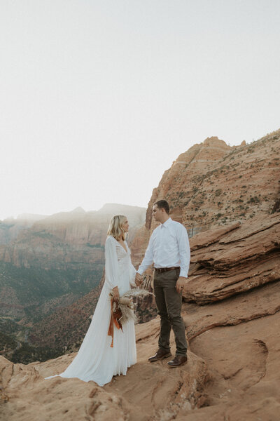Bride and groom holding hands facing each other during their elopement in Zion National Park