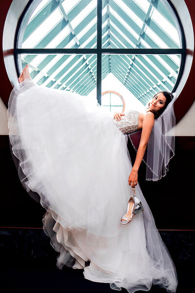 bride-lays-in-window-holding-shoes