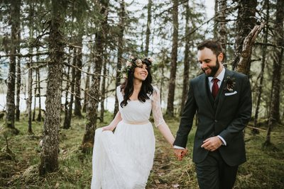 bride and groom walking through the forest in Juneau after their Alaska Elopement