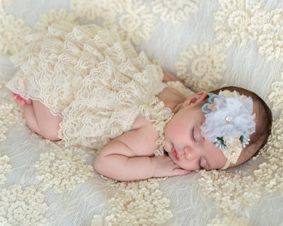 Newborn baby girl sleeping on a lace blanket. Newborn girl portrait session.