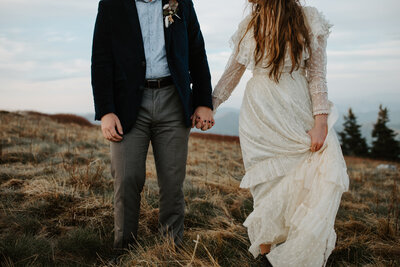bride and groom holding hands on top of a mountain