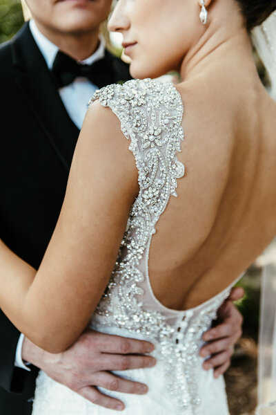 Bride and groom embracing with focus on the low-backed wedding dress