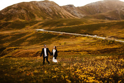 wedding couple walks through hatcher pass surrounded by vivid orange fall leaves